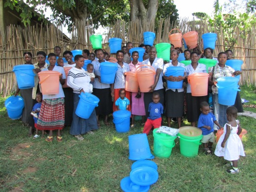 Caregivers and children posing for a group photo after receiving their buckets
